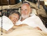 Photo: Older couple sleeping together in bed