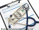 Photo: Dollar bill, stethoscope on an insurance form